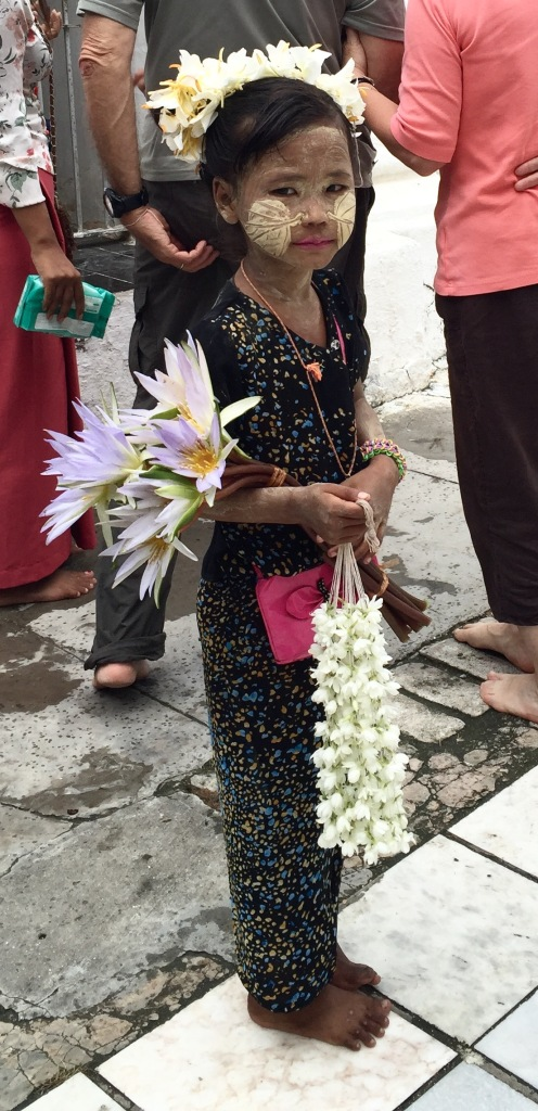 Beautifully adorned little girl, selling flower garlands at the temple.