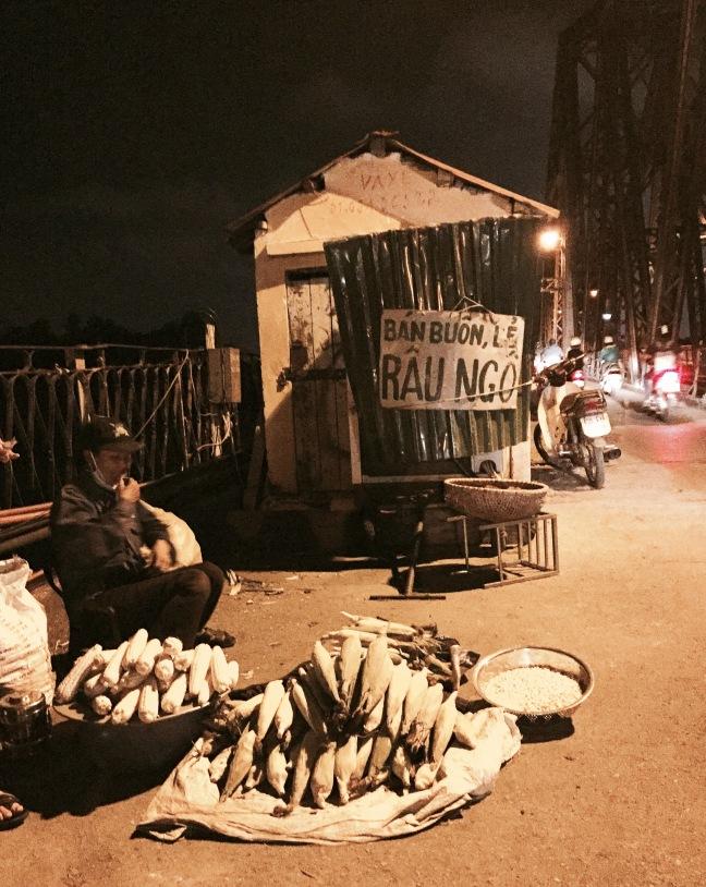 Roadside, roasted corn on the historic Long Bien Bridge.